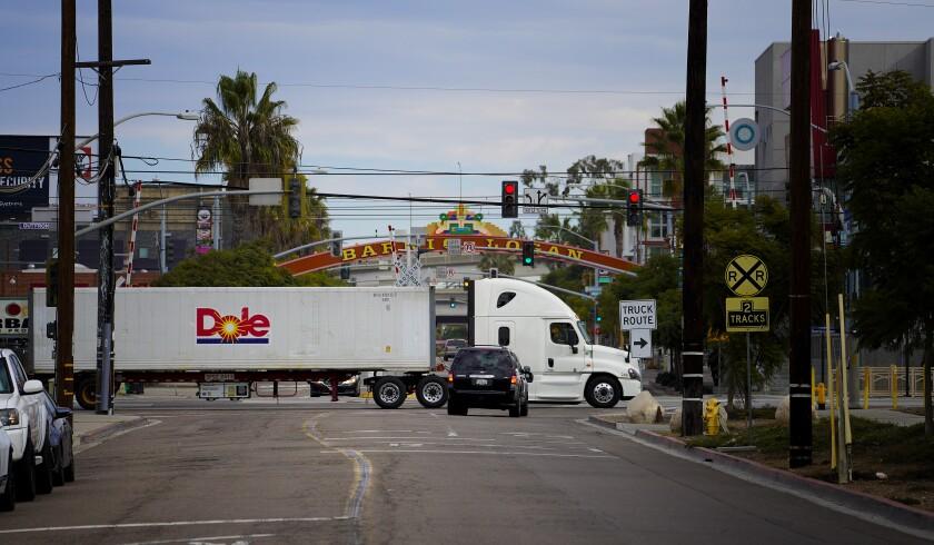 A large semi truck hauls goods along Harbor Drive