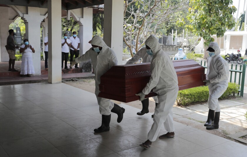 Sri Lankan health workers carry a coffin carrying remains of a COVID -19 victim to a cremation furnace as relatives watch from a distance in Colombo, Sri Lanka, Wednesday, Feb. 10, 2021. (AP Photo/Eranga Jayawardena)