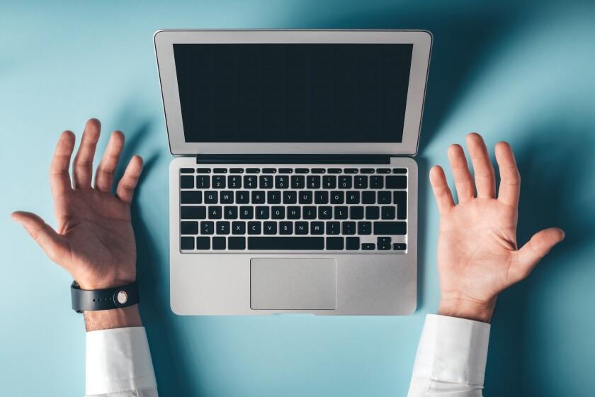 A pair of hands, palms open, flank a laptop.