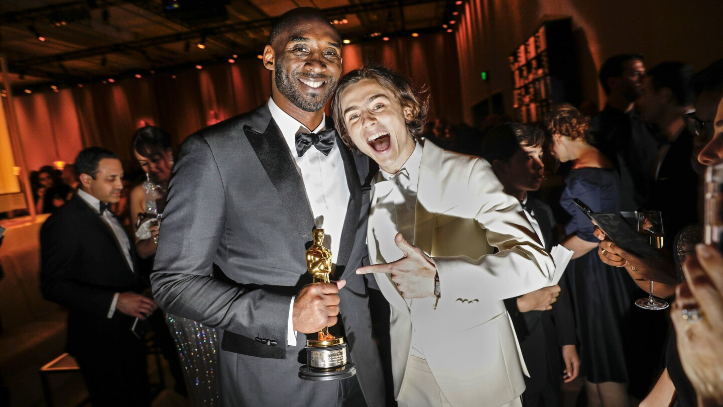 Kobe Bryant holds onto his Oscar as he poses with nominee Timothée Chalamet at the Governors Ball on Sunday.