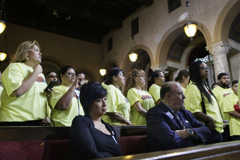 Jim Dunn, foreground right, owner of Airtel Plaza Hotel, who opposes the minimum wage bill, is outnumbered by supporters in yellow shirts when the L.A. City Council tentatively approved a $15.37-per-hour minimum wage for workers at big hotels.