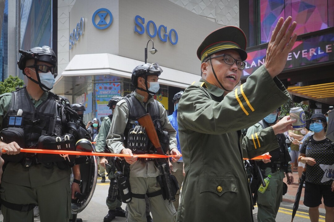 A protester, right, dressed as a Chinese official gestures during a demonstration in Causeway Bay