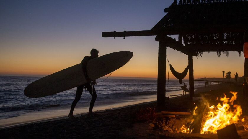 SAN CLEMENT, CA -- TUESDAY, AUGUST 16, 2016: A surfer heads in by a fire pit, hammock and palapa at