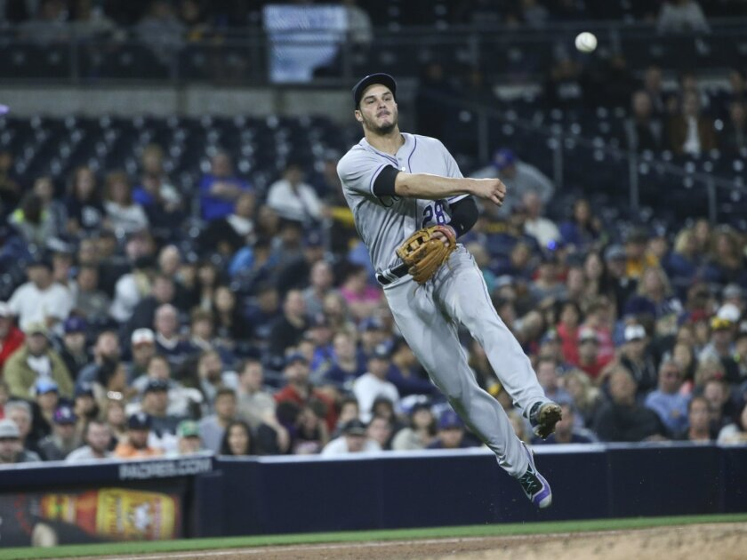 Colorado Rockies third baseman Nolan Arenado throws out San Diego Padres' Alexei Ramirez at first base after fielding a slow roller behind the pitcher's mound in the sixth inning of a baseball game Friday, June 3, 2016, in San Diego. (AP Photo/Lenny Ignelzi)