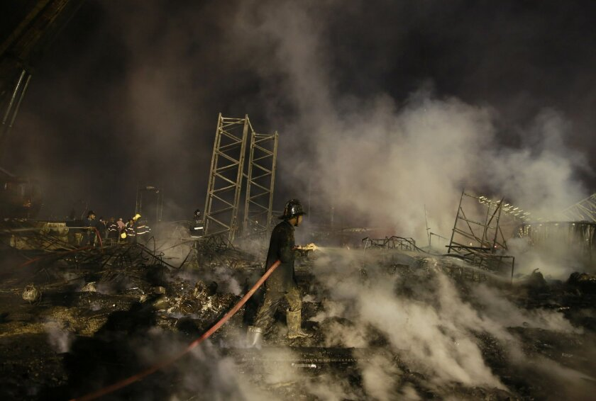 An Indian fire fighter douses a fire which broke out during an event held for Make in India Week in Mumbai, India, Sunday, Feb. 14, 2016. According to news reports a fire broke out on Sunday evening during a cultural programme. (AP Photo/Rafiq Maqbool)