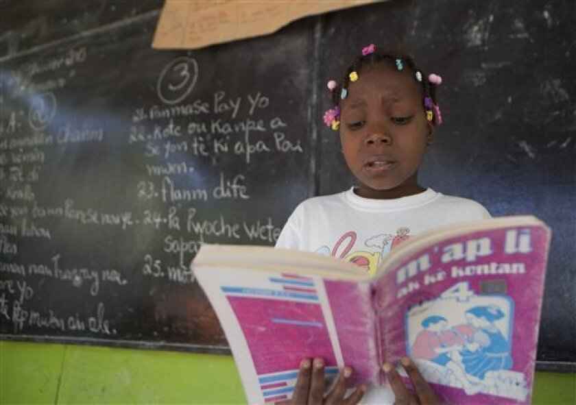 "In this Jan. 24, 2013 photo, Cassandra Meon, 11, reads a textbook before her classmates that reads in Creole ""I'm Reading With a Happy Heart"" as she attends her Creole language class at the Louverture Cleary School, which also teaches French, English and Spanish, in Croix-des-Bouquets, Haiti. Creol"