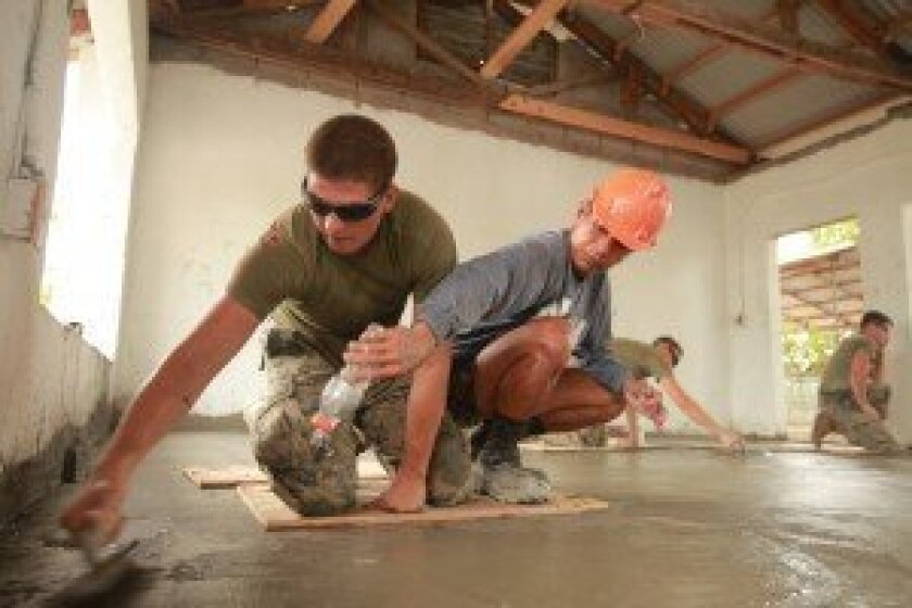 Philippine Navy Seabee Petty Officer Second Class Alfredo Mendoza, right, from the 3rd Naval Construction Battalion, helps Hettrick smooth a concrete pad at the Rabanes Elementary School in 2013. Photo by Staff Sgt. Robert Dea