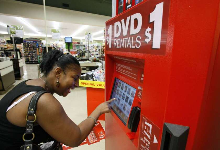 A woman selects a DVD at a Redbox kiosk in 2009. Disney wants the company to stop selling codes for digital versions of its movies.