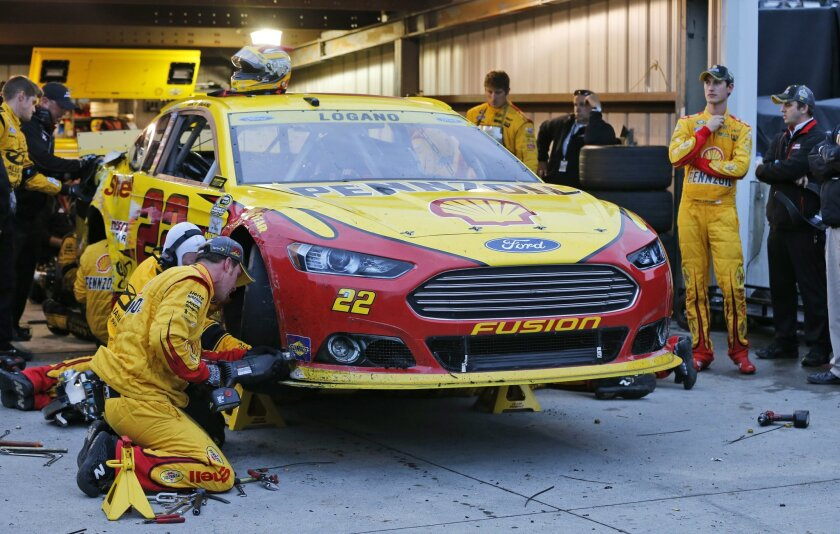 Joey Logano, second from right, watches his crew work on his car after a crash during the NASCAR Sprint Cup Series auto race at Martinsville Speedway in Martinsville, Va., Sunday, Nov. 1, 2015. (AP Photo/Steve Helber)