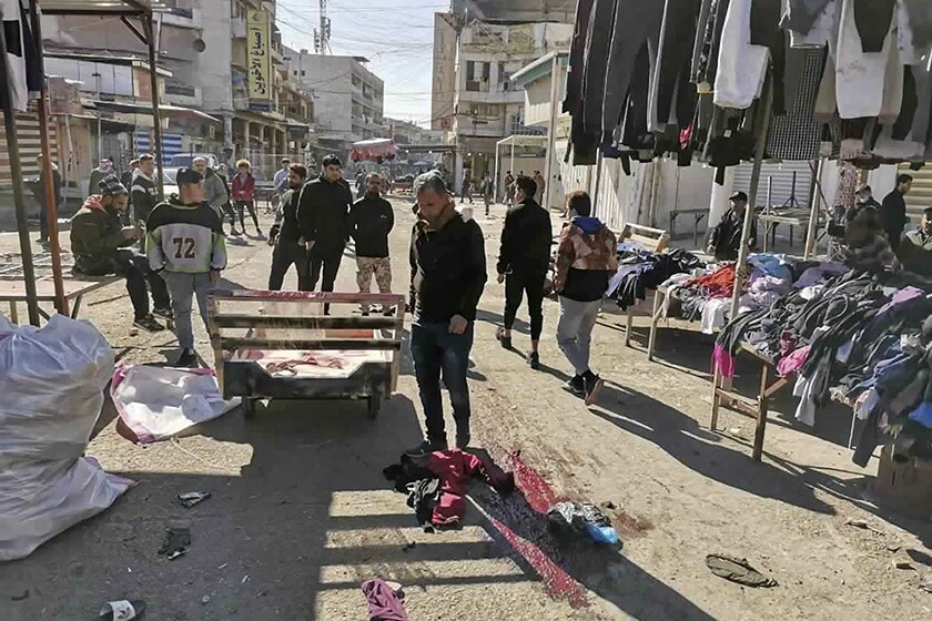 Residents at the scene of Thursday's deadly bomb attack at a Baghdad market.