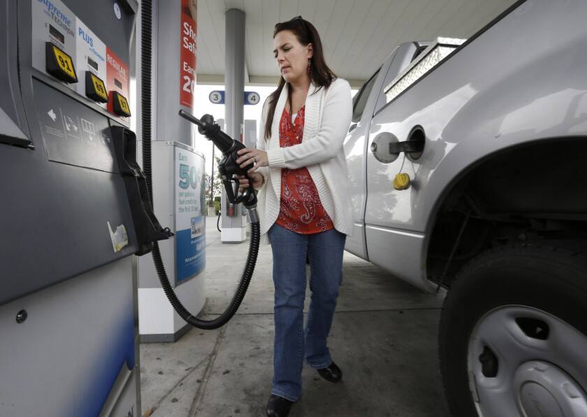 A woman holds the fuel nozzle at a gas station