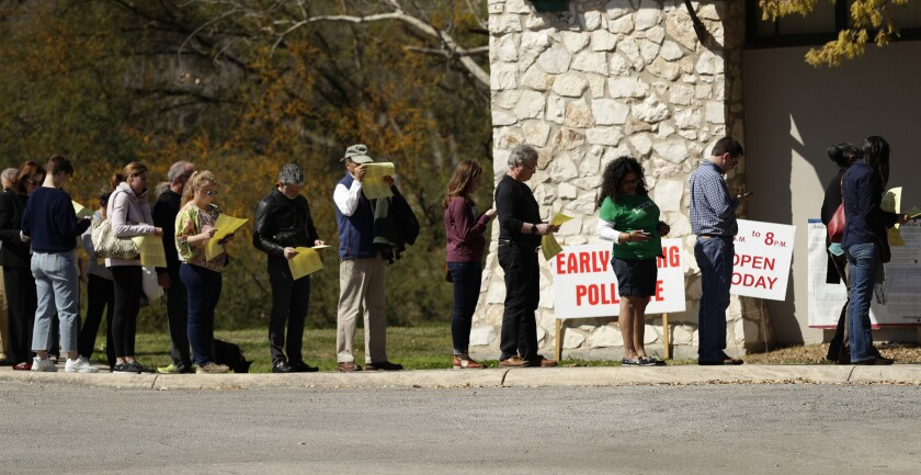 In this Friday, Feb. 28, 2020 photo, voters wait in line at an early polling site in San Antonio. California and Texas are the most populous states in the nation and the biggest delegate prizes for the candidates, yet they also present a stark contrast in voting laws.