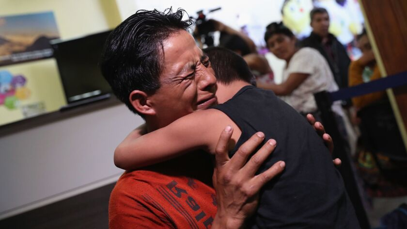 A father embraces his son in Guatemala City. The boy was among nine children flown from New York and reunited with their families in August, months after U.S. border agents deported the parents.