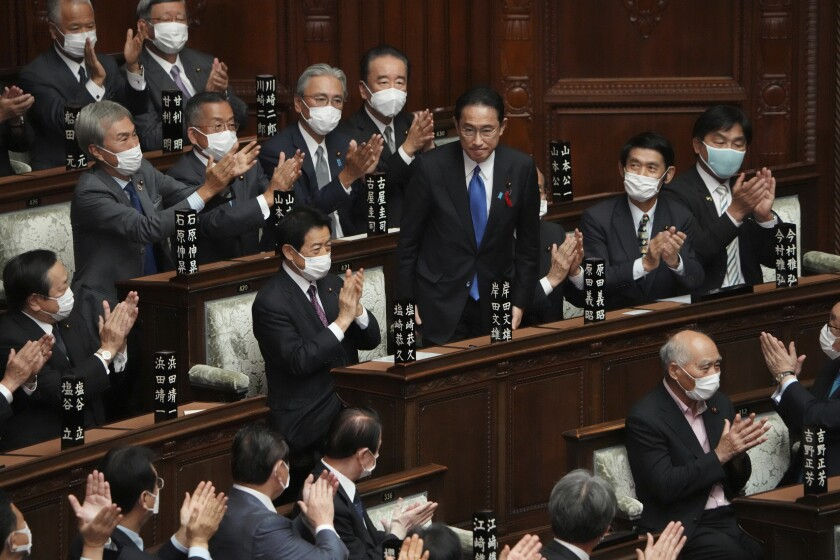 Fumio Kishida, center, is applauded after being elected as Japan's prime minister at the parliament's lower house Monday, Oct. 4, 2021, in Tokyo. Kishida was formally elected Monday as Japan's new prime minister in a parliamentary vote, replacing Yoshihide Suga. (AP Photo/Eugene Hoshiko)