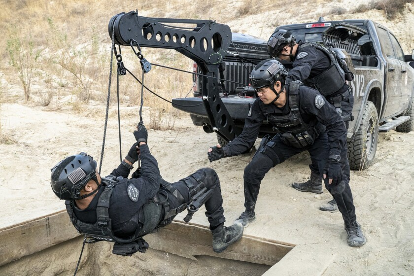"Shemar Moore is lowered on a winch as David Lim watches in ""S.W.A.T."" on CBS."