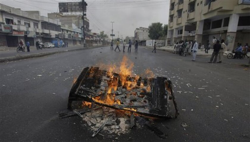 Angry residents burn furniture to protest against the recent killings during a strike in Karachi, Pakistan on Friday, July, 8, 2011. Security forces were ordered to shoot gunmen on sight Friday in Pakistan's largest city, after three days of violence that killed scores of people and prompted political leaders to call for a day of mourning that shut businesses and kept public traffic off the roads. (AP Photo/Fareed Khan)