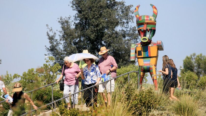 """Visitors look at """"Pretty Boy,"""" a sculpture in the first phase of the Newport Beach Civic Center Park public art exhibition in 2014."""