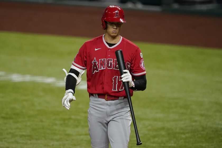 Angels' Shohei Ohtani looks down at his bat after striking out during a Sept. 9 game against the Texas Rangers.