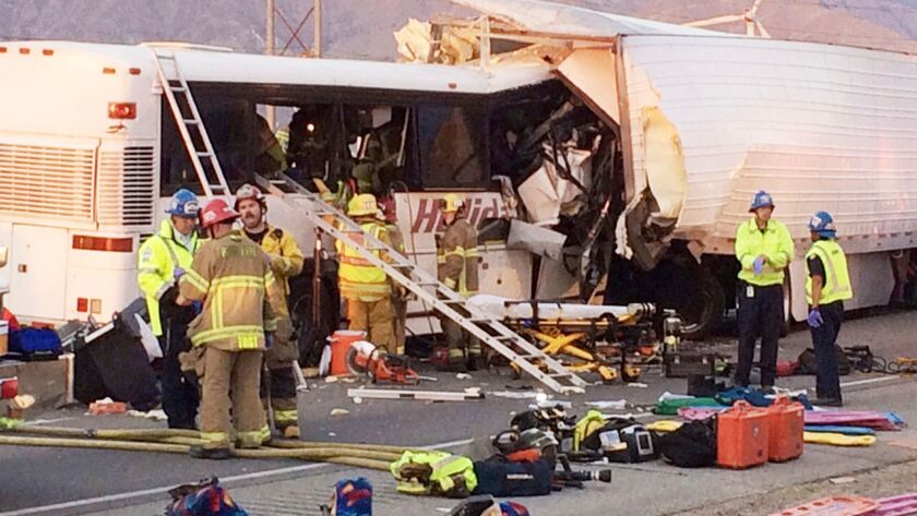 Emergency personnel work the scene where a tour bus crashed into the rear of a semi-truck on westbou