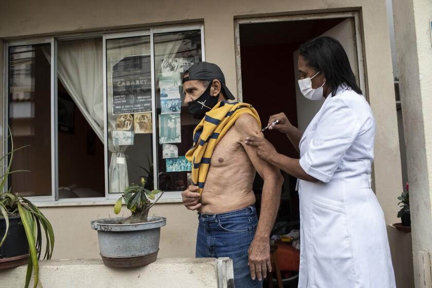 André Luiz da Silva, de 70 años, recibe la vacuna contra el COVID-19 desarrollada por Pfizer y BioNTech como parte de una campaña para administrar una tercera dosis de refuerzo a los mayores que viven en centros, en un retiro para artistas jubilados, en Río de Janeiro, Brasil, el 1 de septiembre de 2021. (AP Foto/Bruna Prado)