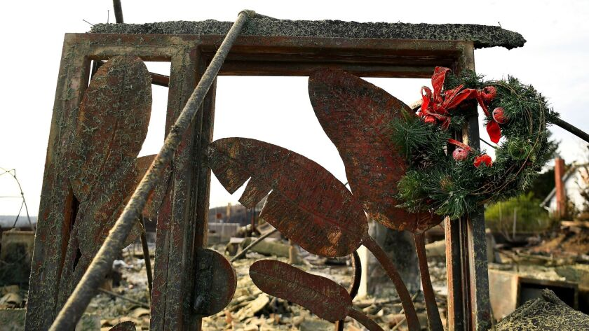 VENTURA, CALIFORNIA DECEMBER 24, 2017-A Christmas wreath hangs from a doorway of a burned house alon
