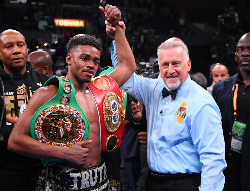 Referee Jack Reiss in in the ring with Erroll Spence Jr. after he defeated Shawn Porter (not pictured) in their IBF & WBC World Welterweight Championship fight at Staples Center on Saturday.
