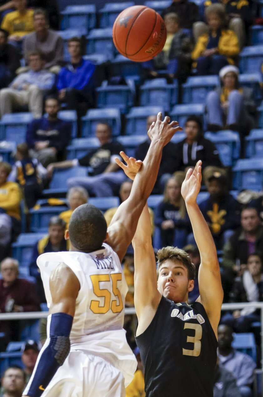 FILE - In this Dec. 19, 2012, file photo ,West Virginia's Keaton Miles (55) fouls Oakland's Travis Bader (3) as he shoots during the second half of an NCAA college basketball game at WVU Coliseum in Morgantown, W.Va. Bader needs eight 3-pointers to break J.J. Redick's career record for a Division I player. That would be quite an accomplishment for a player who admits he wasn't ready to play at this level when he first arrived at Oakland and redshirted his first year. (AP Photo/David Smith, File)