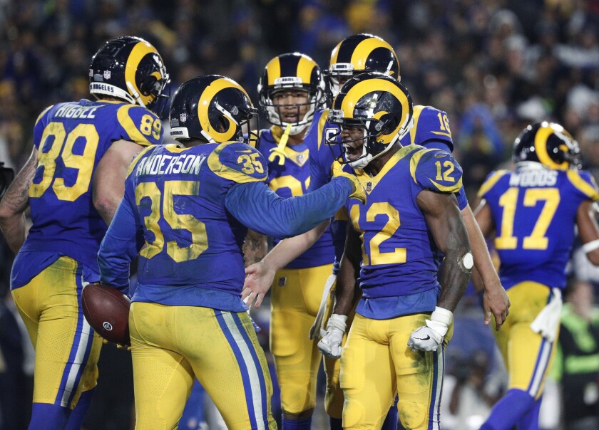 Rams running back C.J. Anderson (35) celebrates with receiver Brandin Cooks (12) and other teammates after he scored a touchdown on a fourth-down play during the fourth quarter.