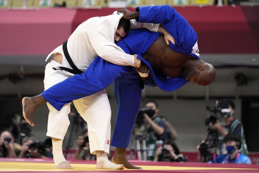 Tamerlan Bashaev of the Russian Olympic Committee, left, and Teddy Riner of France compete during their men's +100kg elimination round judo match at the 2020 Summer Olympics, Friday, July 30, 2021, in Tokyo, Japan. (AP Photo/Vincent Thian)