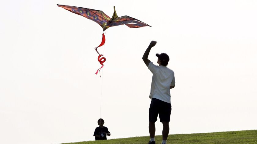 (Published 5/18/2005, B-4:1,7) Frank Ruff flew a kite with his son David, 7, at Mission Bay Park on