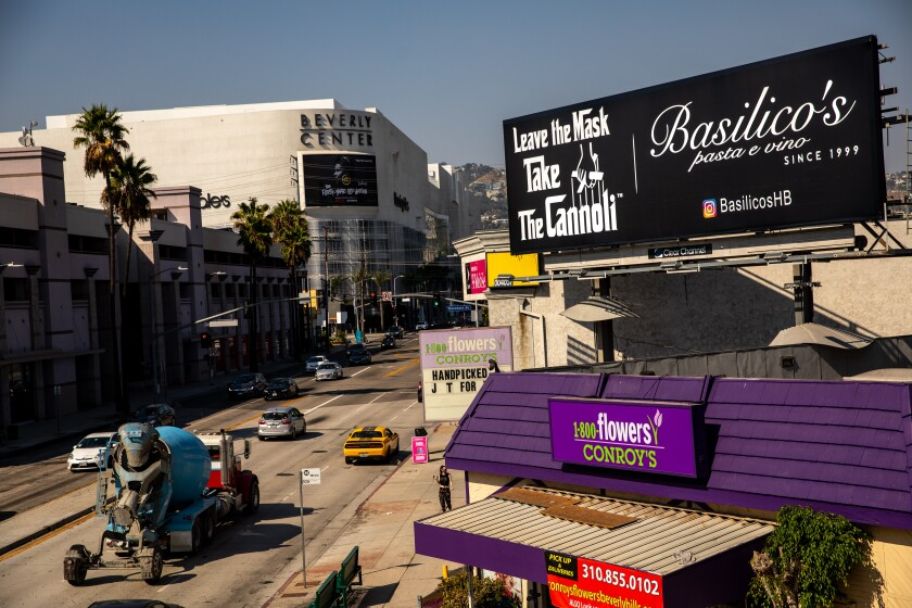 """A billboard with white letters and a black background reads """"Leave the mask, take the cannoli,"""" and """"Basilico's pasta e vino"""""""
