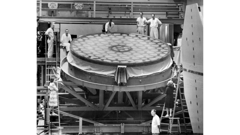 Dec. 3, 1945: Workers pose with the mirror of the 200-inch telescope at the Caltech Optical Shop in Pasadena when grinding work was resumed after the end of World War II.