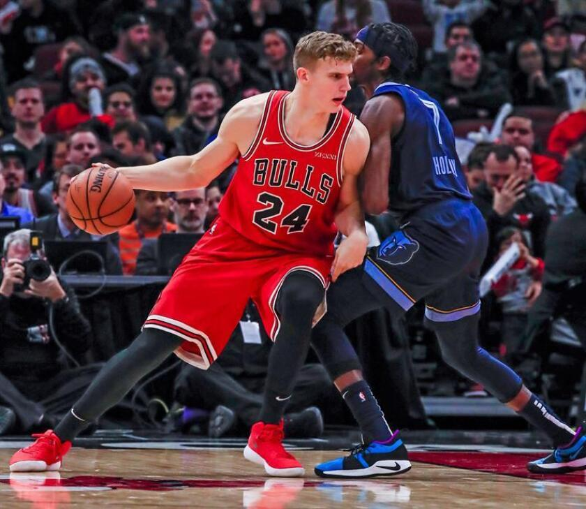 El alero de los Bulls de Chicago Lauri Markkanen de Finlandia (i) intenta maniobrar en el alero de los Grizzlies de Memphis Justin Holiday (d) durante el partido de la NBA en el United Center de Chicago. EFE