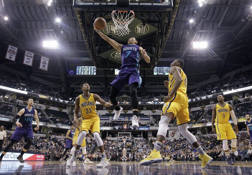 Charlotte Hornets' Jeremy Lin (7) puts up a shot against Indiana Pacers' Myles Turner (33) and Glenn Robinson III (40) during the second half of an NBA basketball game Wednesday, Feb. 10, 2016, in Indianapolis. Charlotte won 117-95. (AP Photo/Darron Cummings)