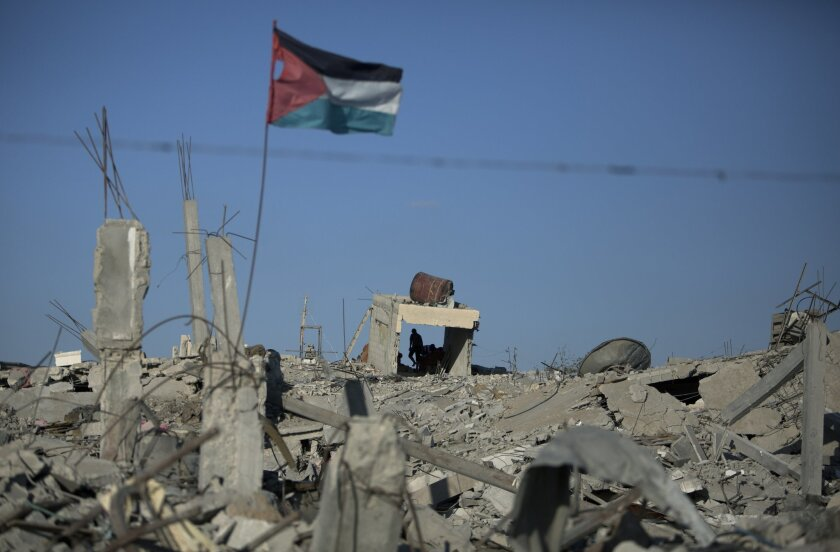 In this Wednesday, Oct. 1, 2014 photo, a Palestinian flag waves as a man walks over the rubble of houses that were destroyed in the recent Israel-Hamas war, in Khuzaa, southern Gaza Strip. More than five weeks after the war in the Gaza Strip, tens of thousands of people whose homes were destroyed or badly damaged in the fighting still live in classrooms, storefronts and other crowded shelters. Yet despite their pressing needs, reconstruction efforts appear stymied by a continued Israeli-Egyptian border blockade of Gaza and an unresolved power struggle between the Islamic militant group Hamas and Western-backed Palestinian President Mahmoud Abbas. (AP Photo/Khalil Hamra)