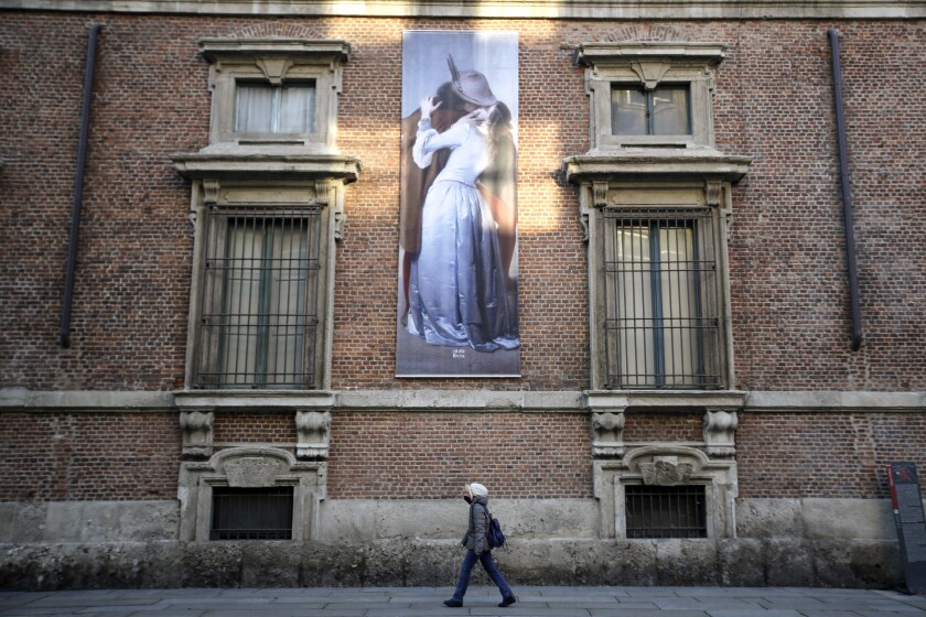 A woman walks past a poster depicting the 1859 painting by Italian artist Francesco Hayez, ll Bacio (The Kiss), hanging on a facade of the Pinacoteca di Brera Museum, in Milan, Italy, Wednesday, March 11, 2020. Italy is mulling even tighter restrictions on daily life and has announced billions in financial relief to cushion economic shocks from the coronavirus. Premier Giuseppe Conte says he will consider requests to toughen an already extraordinary lockdown For most people, the new coronavirus causes only mild or moderate symptoms, such as fever and cough. For some, especially older adults and people with existing health problems, it can cause more severe illness, including pneumonia. (AP Photo/Luca Bruno)