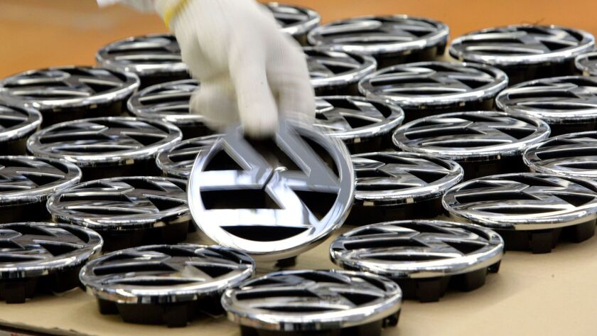The EPA and the California Air Resources Board had to approve the fix under a $1.2-billion settlement approved by a federal judge this spring. Above, a worker takes a VW-emblem at the Volkswagen factory in Wolfsburg, Germany.