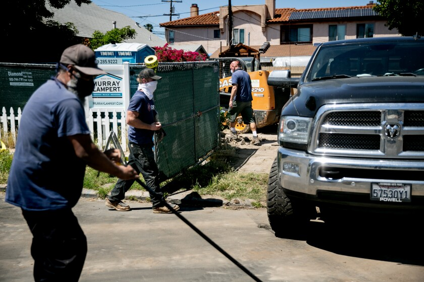 A demolition crew from Construction Support Services works on the tear down of a home on Monroe Avenue in the University Heights neighborhood Monday in San Diegoa.
