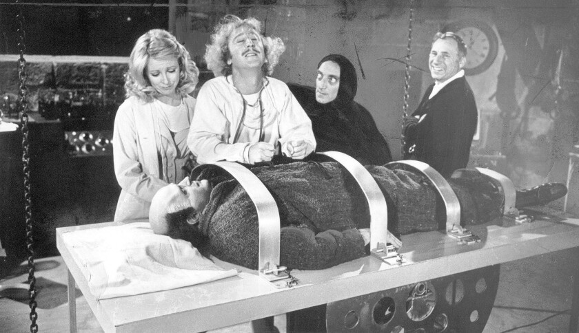 """Director Mel Brooks, right, on the set of his 1974 classic """"Young Frankenstein"""" with a prone Peter Boyle, Teri Garr, Gene Wilder and Marty Feldman."""