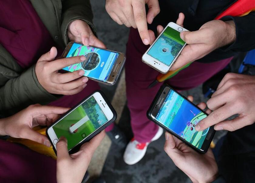Vista de un grupo de gente jugando con sus teléfonos móviles. EFE/Archivo