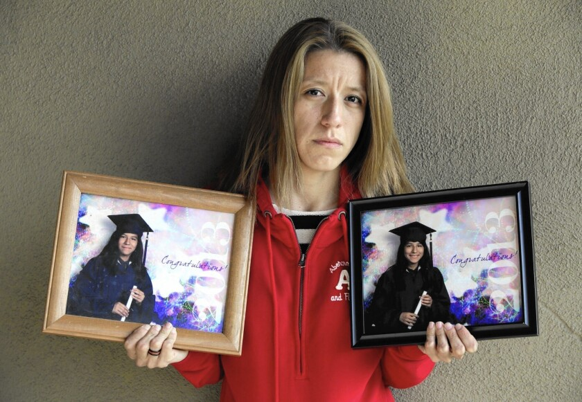 Magaly Huerta holds photos of her nieces, twins Lexandra, left, and Lexi Perez, from their elementary school graduation.