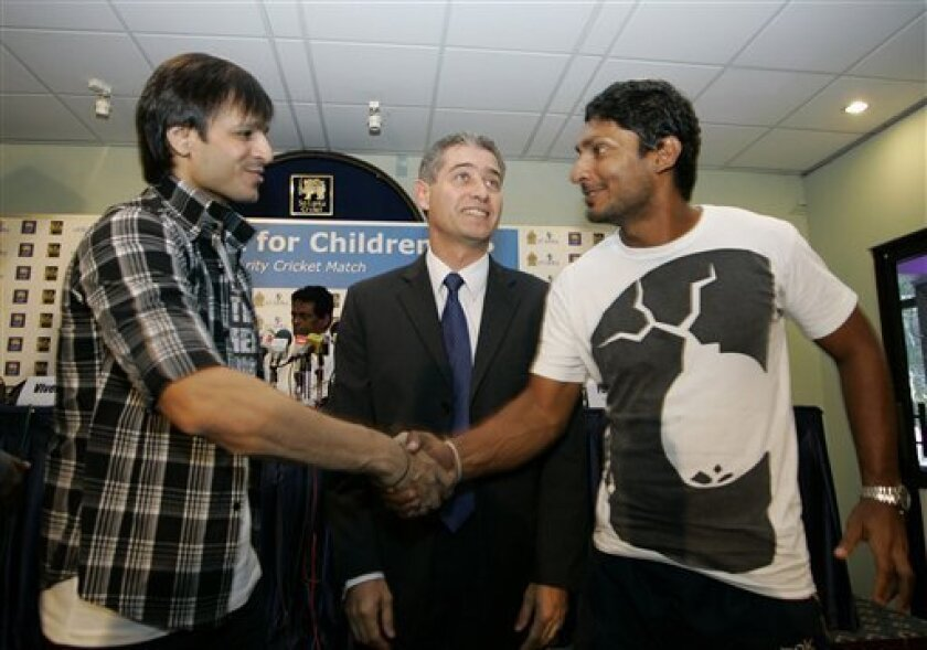 Sri Lankan cricket captain Kumar Sangakkara, right, shakes hands with Bollywood actor Vivek Oberoi, left , as UNICEF country representative Philippe Duamelle, center, looks on during a press conference held to announce a celebrity cricket match promoting Indian International Film Academy awards in Colombo, Sri Lanka, Wednesday, June 2, 2010. (AP Photo/Eranga Jayawardena)