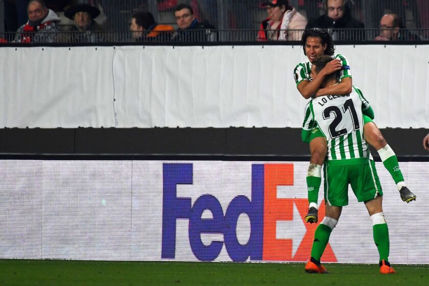 Real Betis' Spanish midfielder Diego lainez (top) celebrates with Real Betis' Spanish midfielder Giovanni Lo Celso after scoring a goal during the UEFA Europa League round of 32 first-leg football match between Rennes and Real Betis at the Roazhon Park stadium in Rennes, western France, on February 14, 2019.