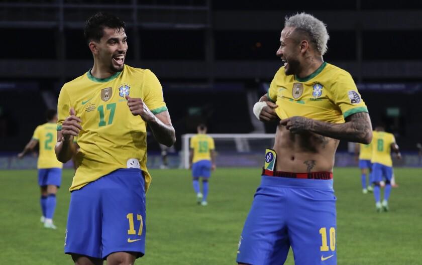 Brazil's Lucas Paqueta, left, celebrates with teammate Neymar after scoring his side's opening goal against Peru during a Copa America semifinal soccer match at Nilton Santos stadium in Rio de Janeiro, Brazil, Monday, July 5, 2021. (AP Photo/Silvia Izquierdo)