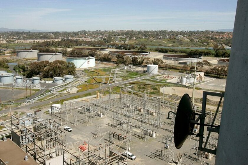 Proposed site of NRG power plant, from roof of the landmark Encina Power Station. The plant would be built where the three large tanks are in the distance. In foreground is an SDG&E switching station. At right is a microwave dish antenna on the power station's smokestack.