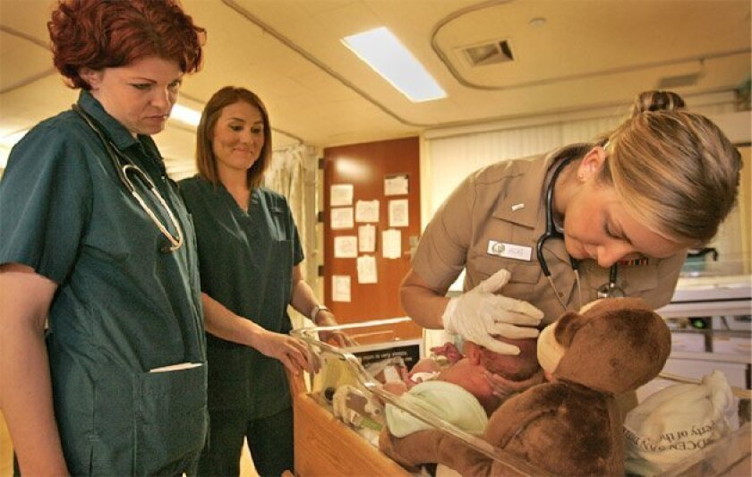 San Diego City College nursing students Laura Dorrance (left) and Jessica Levitan watched Ensign Chelsea Hicks, a nurse intern, examine a newborn at the San Diego Naval Medical Center. (Howard Lipin / Union-Tribune)