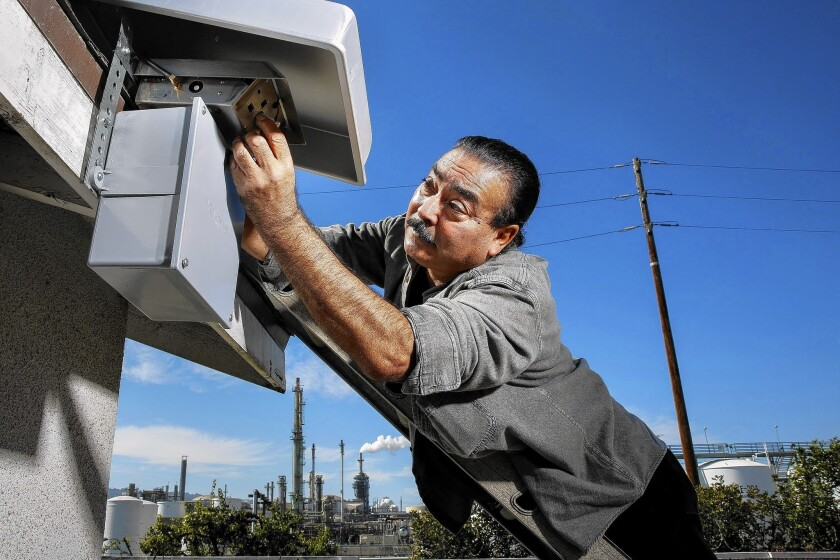 Jesse Marquez, executive director of Coalition for a Safe Environment, installs an air-quality device on the Peleti family's home in Wilmington near the Phillips 66 oil refinery.