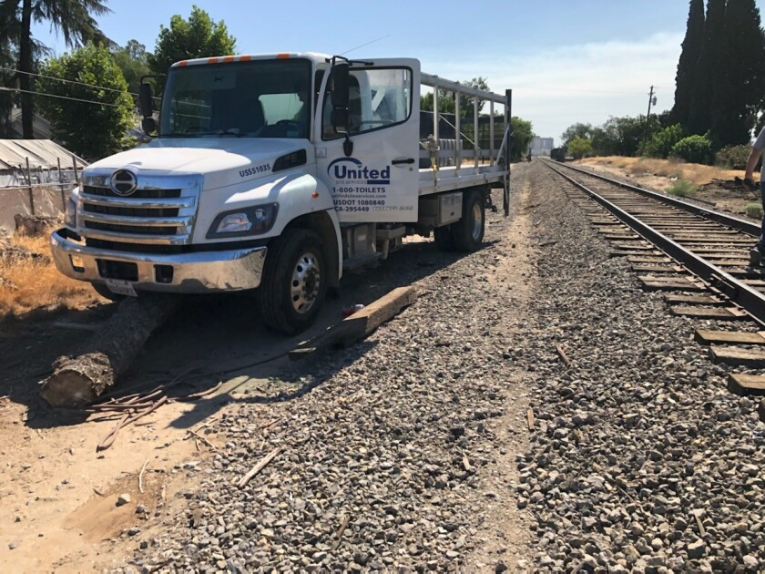 A truck with a door open sits next to railroad tracks.