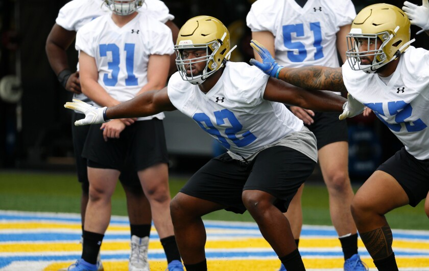 UCLA defensive lineman Osa Odighizuwa, left, takes part in drills at training camp.