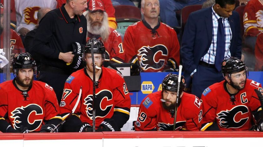 Calgary Flames players watch from the bench as the Anaheim Ducks celebrate their overtime victory du
